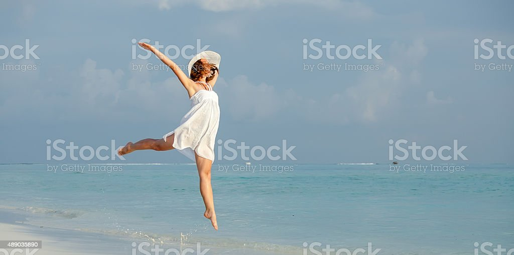 Happy young woman jumping on the beach stock photo