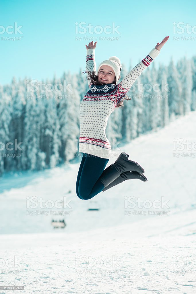 Happy Young Woman Jumping on the Snow with Raised Arms stock photo