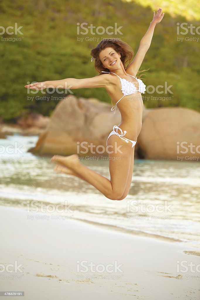 Happy young woman jumping while enjoying on beach royalty-free stock photo