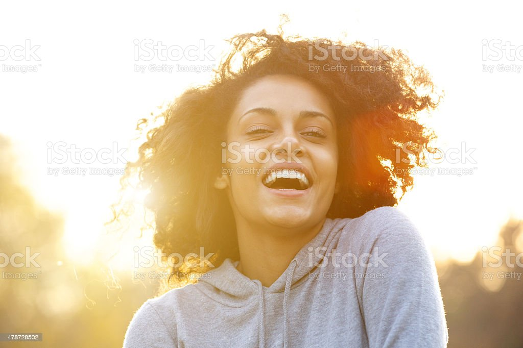 Happy young woman laughing outdoors stock photo