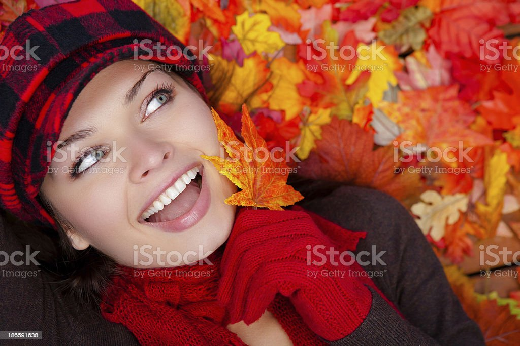 Happy young woman laying on autumn leaves royalty-free stock photo