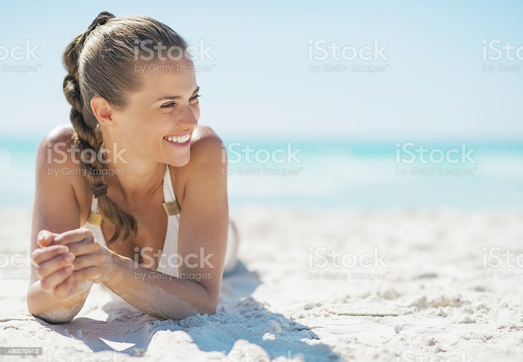 Happy young woman laying on beach stock photo