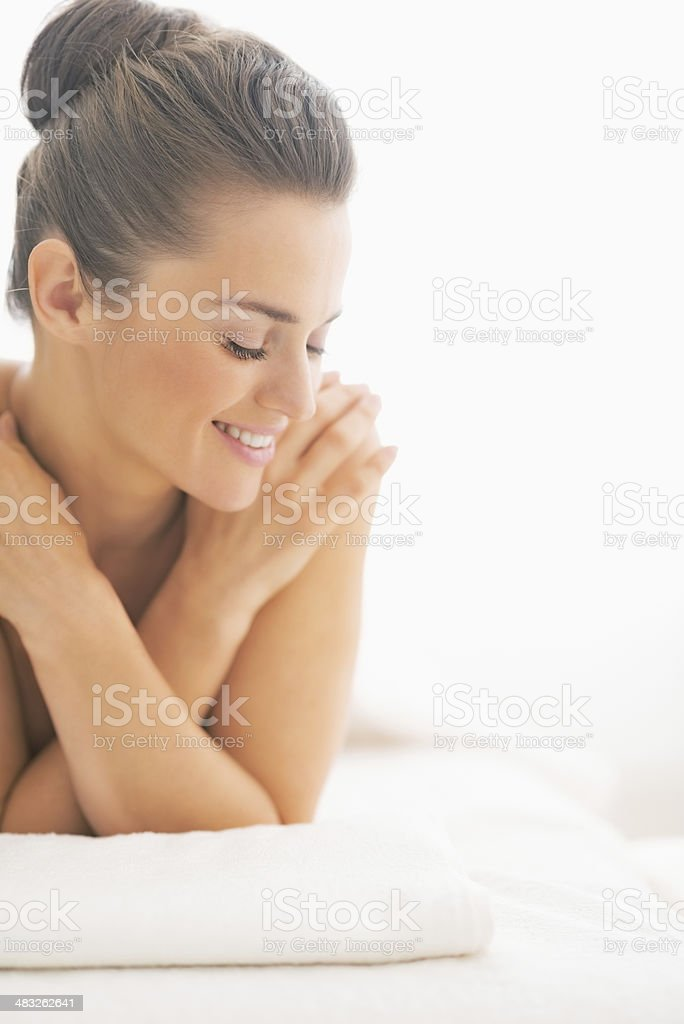 happy young woman laying on massage table stock photo