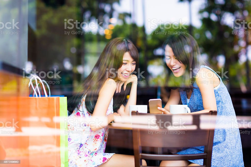 happy young woman looking at phone in coffee shop stock photo