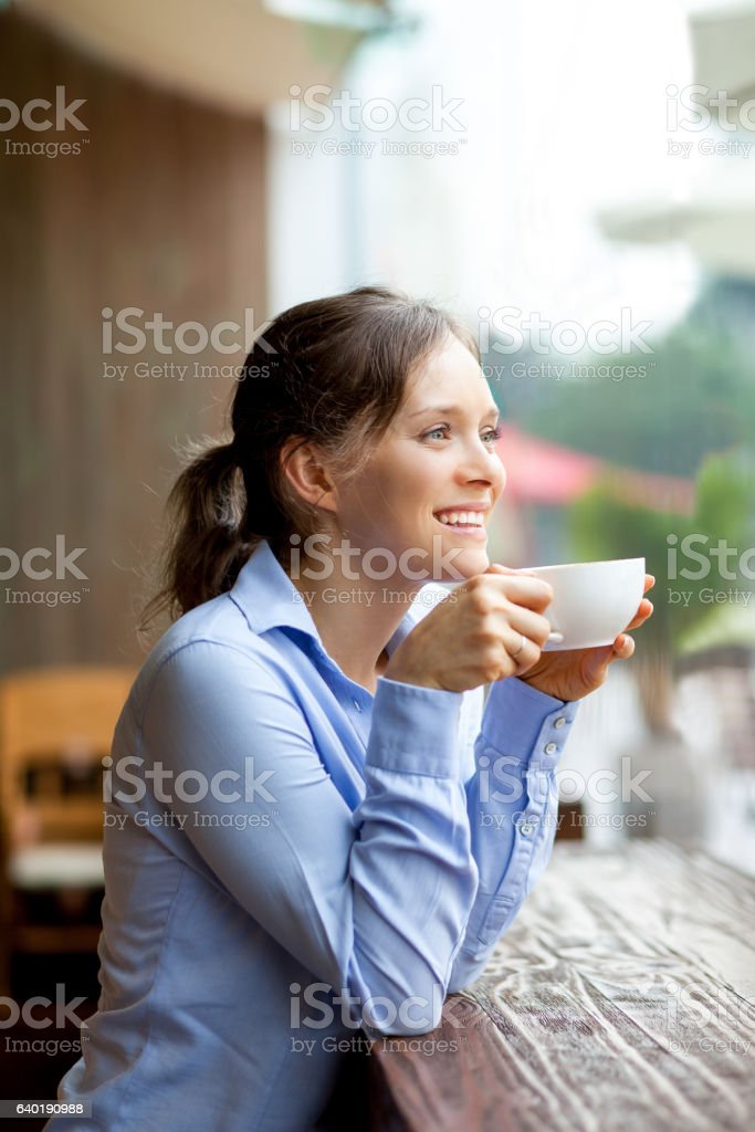 Happy young woman looking through window stock photo