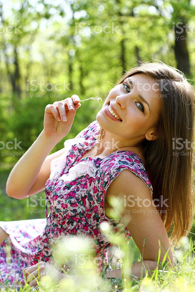 Happy young woman lying in meadow on warm summer day royalty-free stock photo