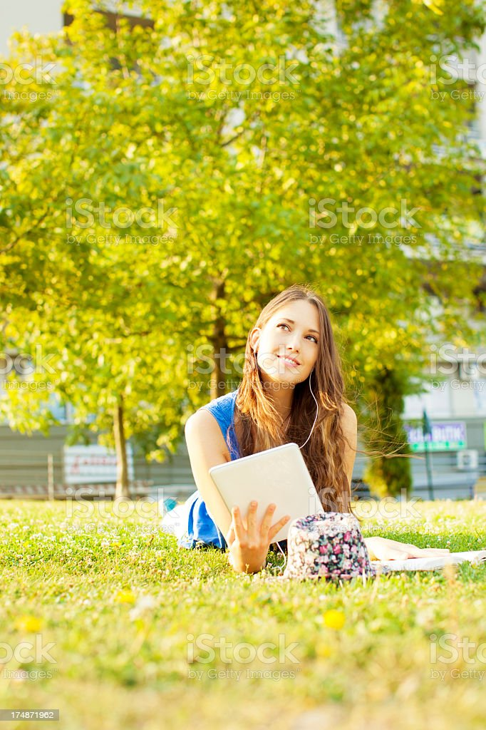 Happy Young Woman lying on grass and listening music. royalty-free stock photo