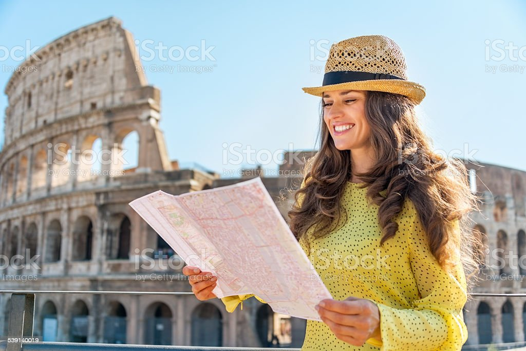 Happy young woman near colosseum in rome, italy stock photo