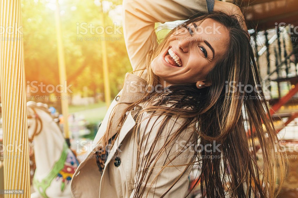 Happy young woman on a carousel stock photo
