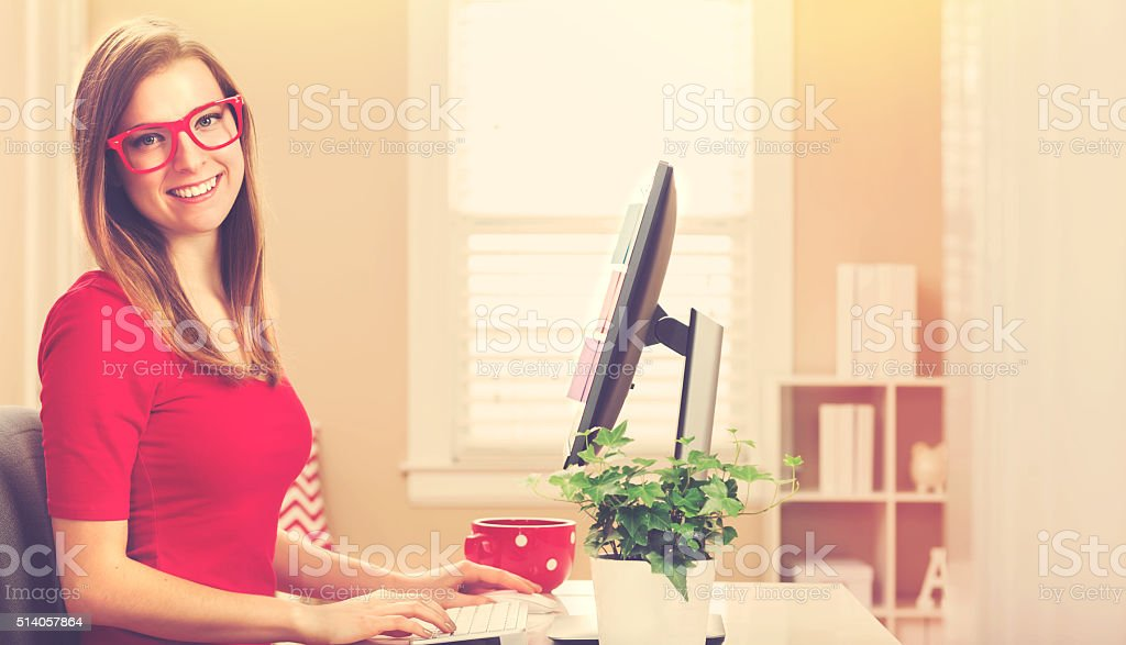 Happy young woman on her computer in her home office stock photo