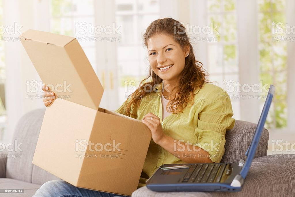 Happy young woman opening package at home royalty-free stock photo
