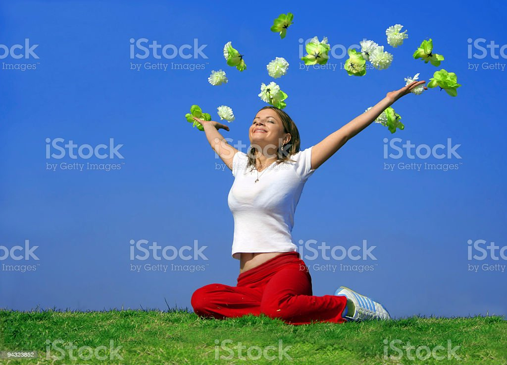 Happy young woman outdoor with flying flowers stock photo