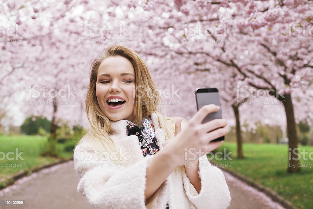 Happy young woman photographing herself at park stock photo