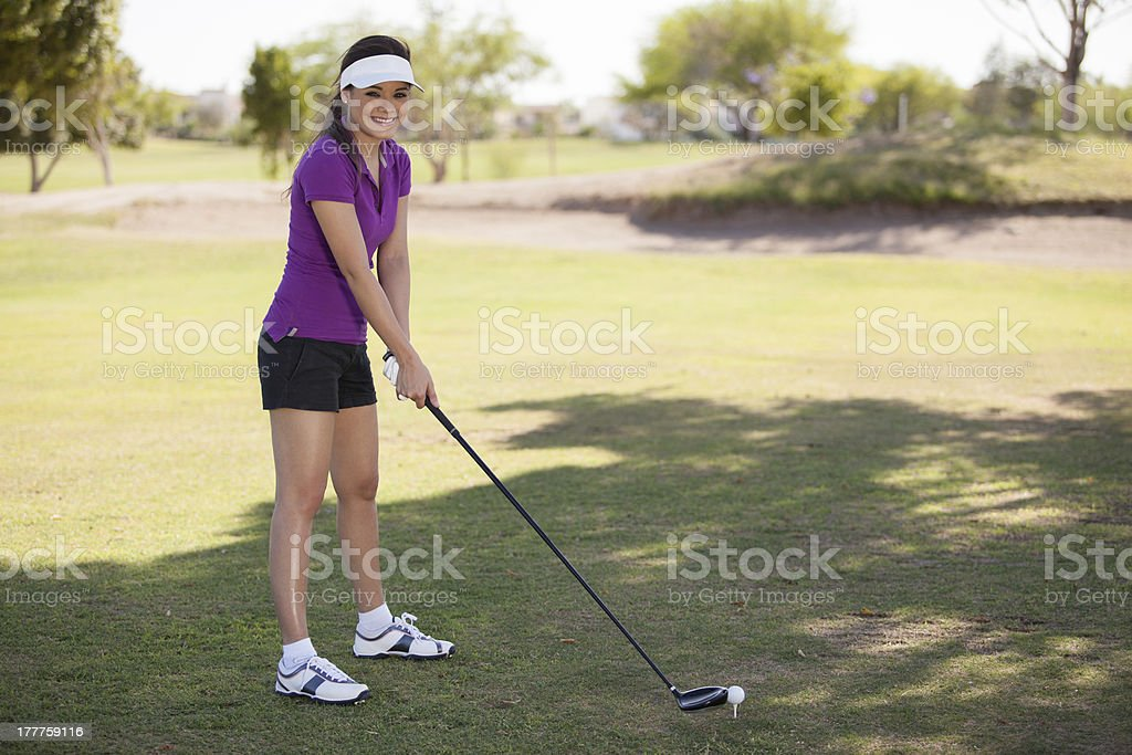 Happy young woman playing golf royalty-free stock photo