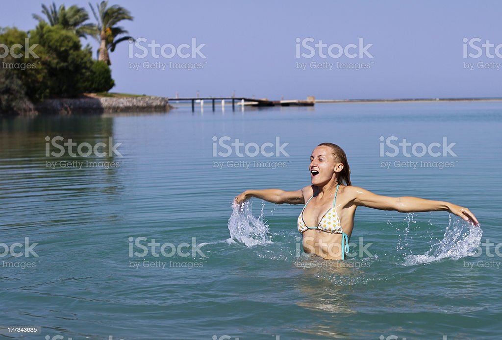 Happy young woman playing in the sea royalty-free stock photo