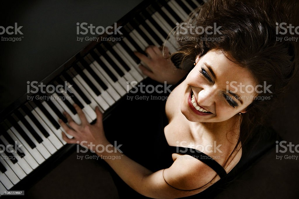 Happy Young Woman Playing Piano stock photo