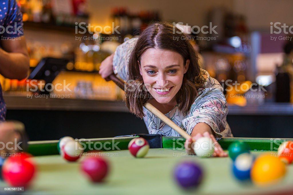 Happy Young Woman Playing Pool in a Bar stock photo