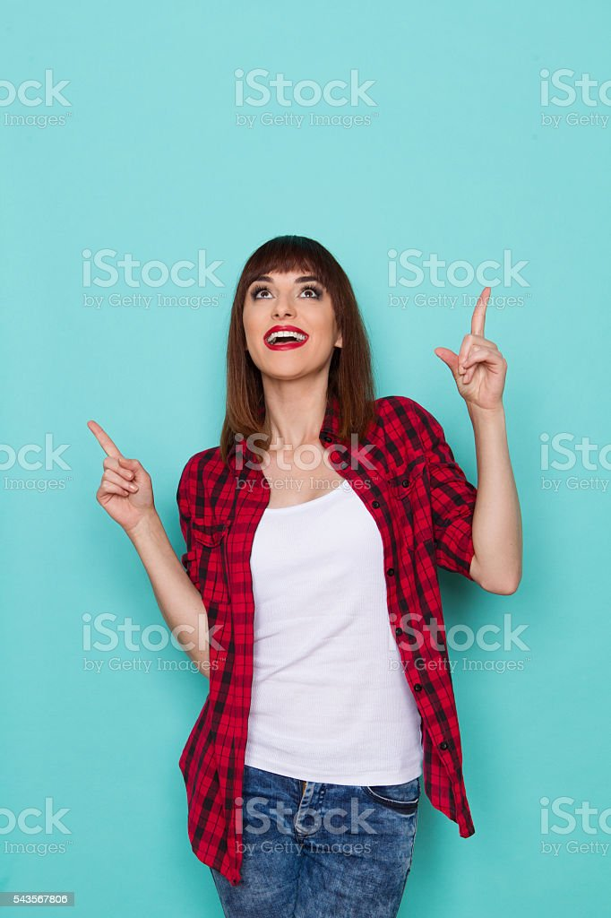 Happy Young Woman Pointing Above Head stock photo