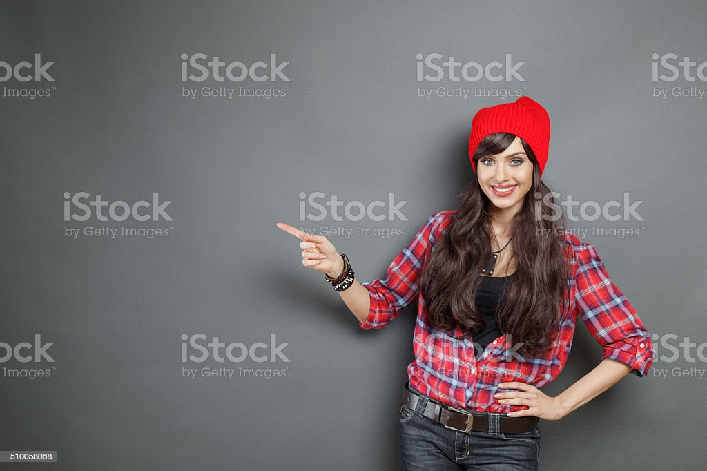 Happy young woman pointing at copy space stock photo