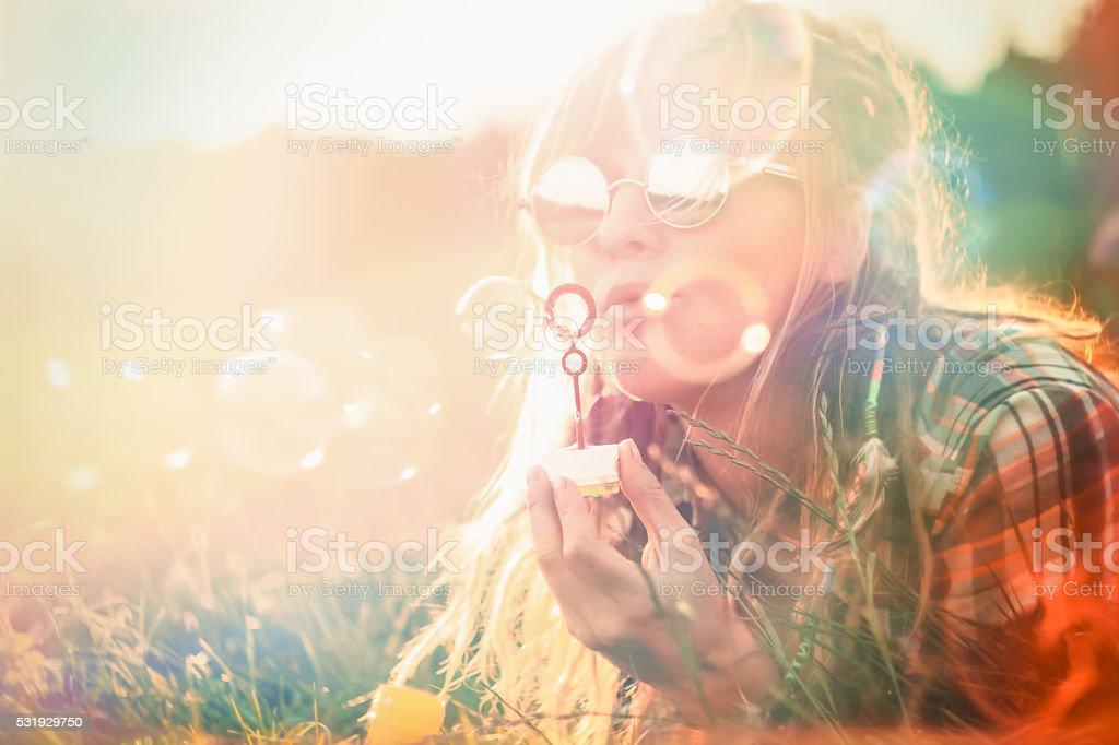 Happy young woman portrait blowing soap bubbles stock photo