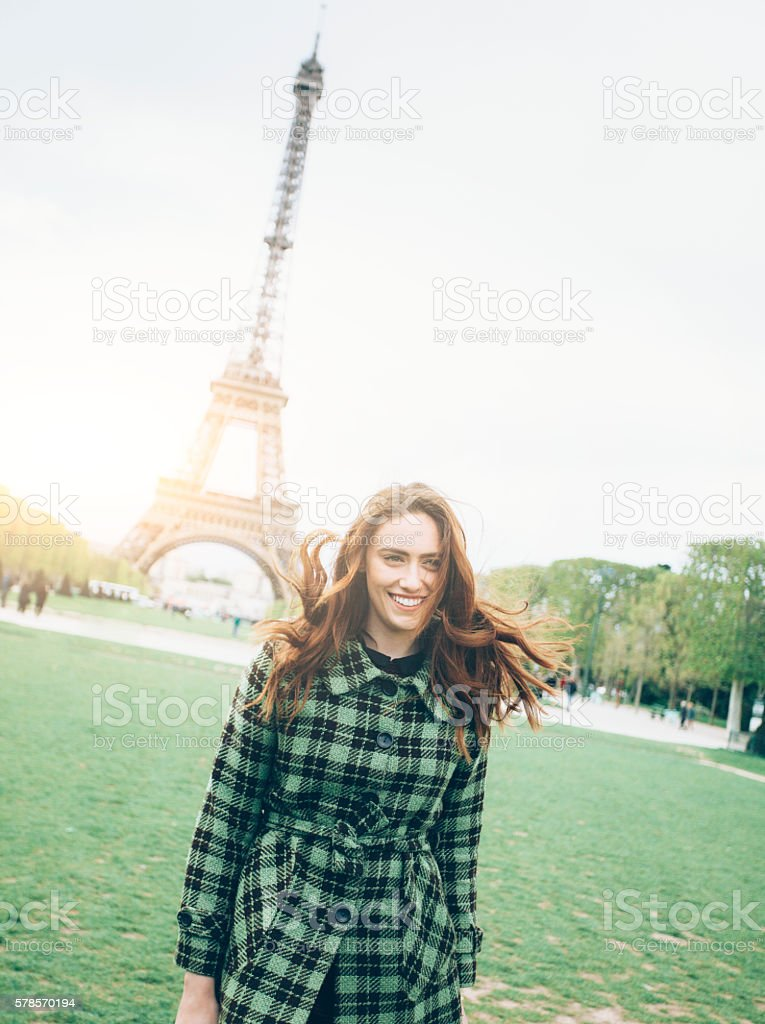 Happy young woman posing in front of Eiffel tower stock photo