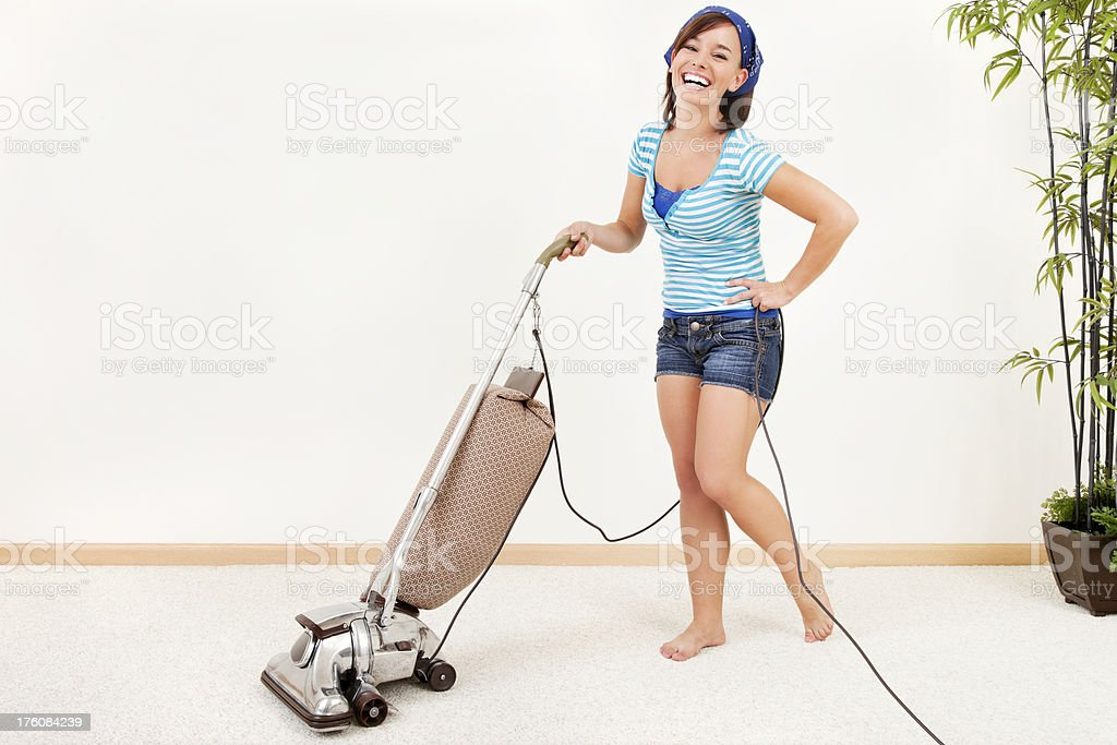 Happy Young Woman Pushing Vacuum Cleaner royalty-free stock photo