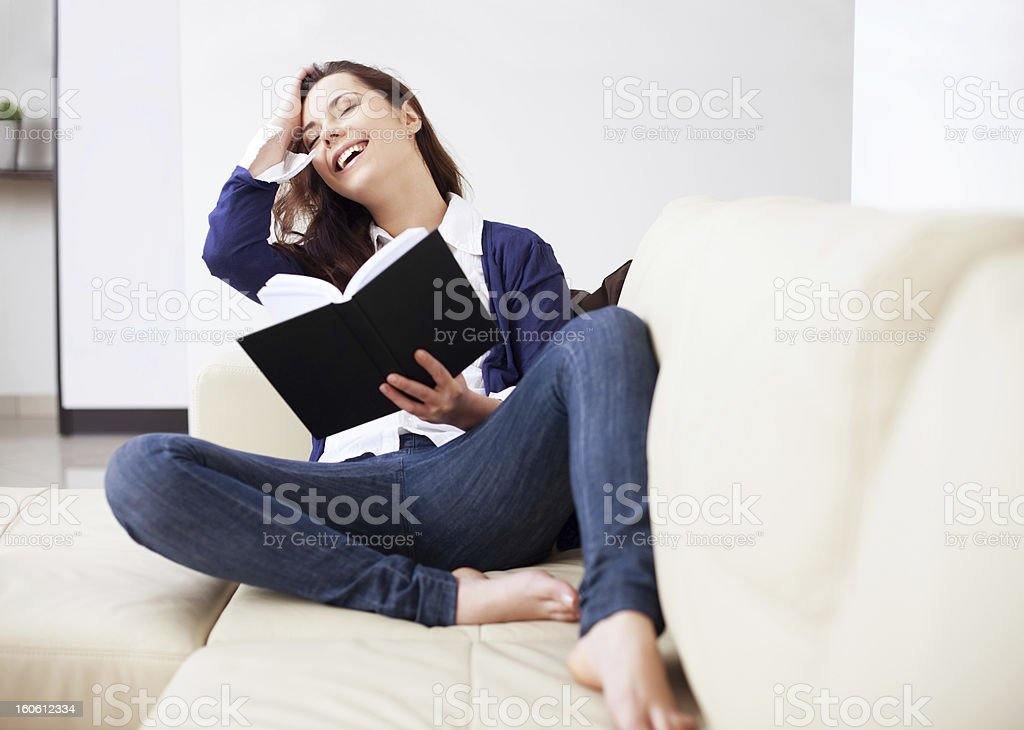 Happy young woman reading a book at home royalty-free stock photo