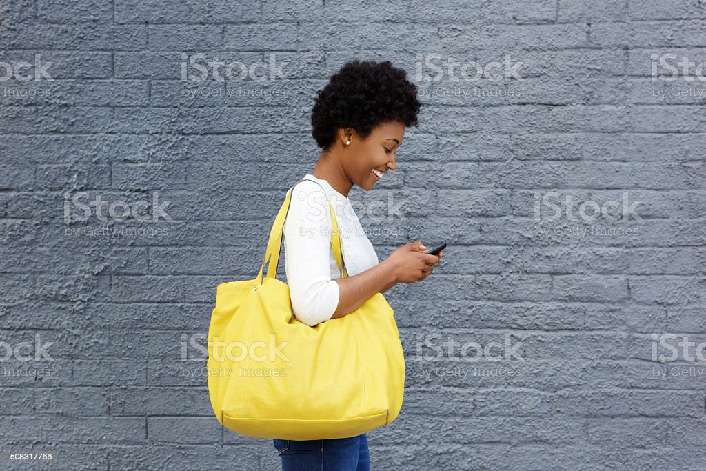 Happy young woman reading text message on mobile phone stock photo