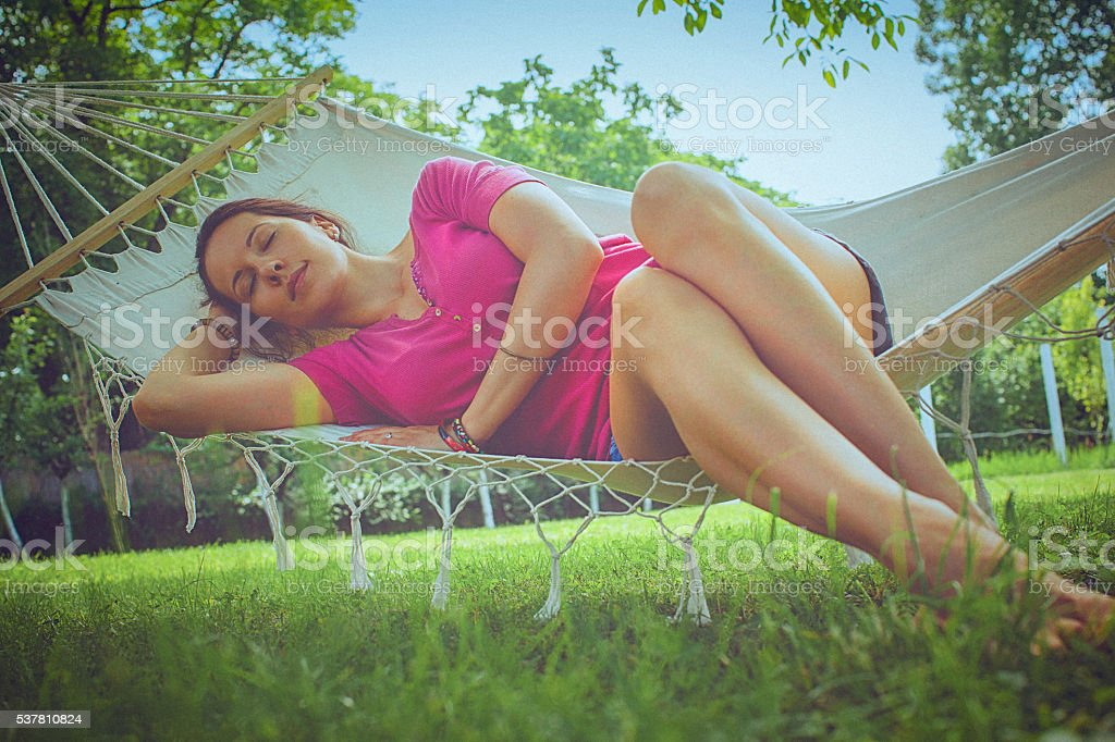 Happy young woman relaxing in a hammock in the garden stock photo