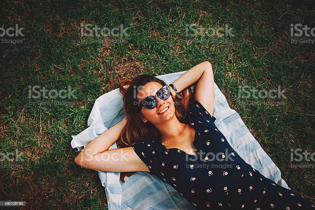 Happy young woman relaxing on grass stock photo