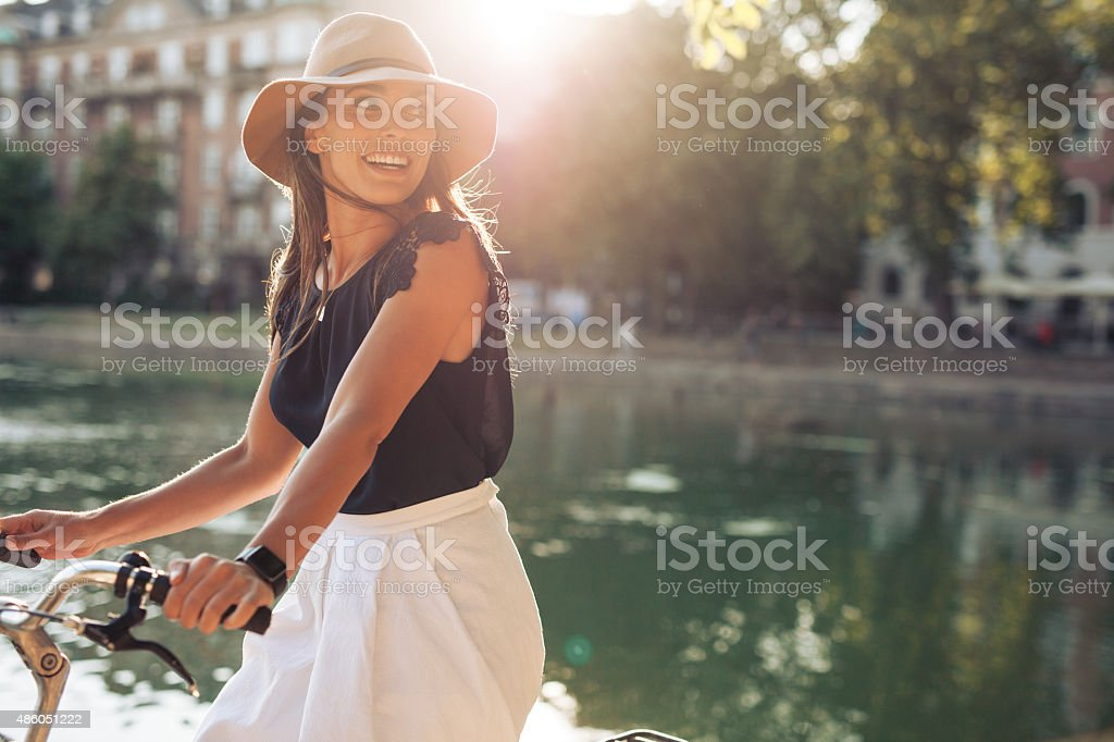 Happy young woman riding bicycle by a pond stock photo