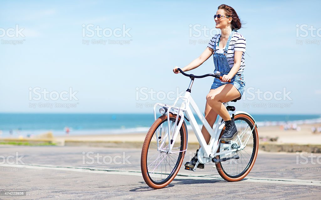 happy young woman riding bike near North sea stock photo