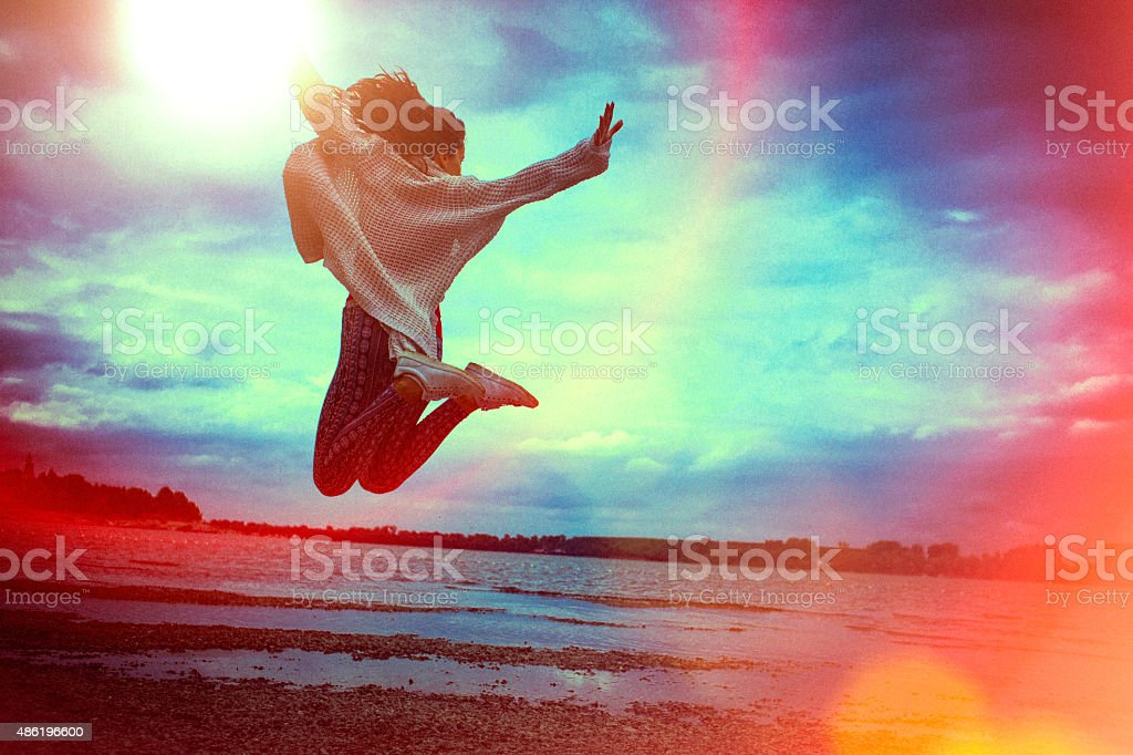 Happy young woman running and jumping on the beach stock photo
