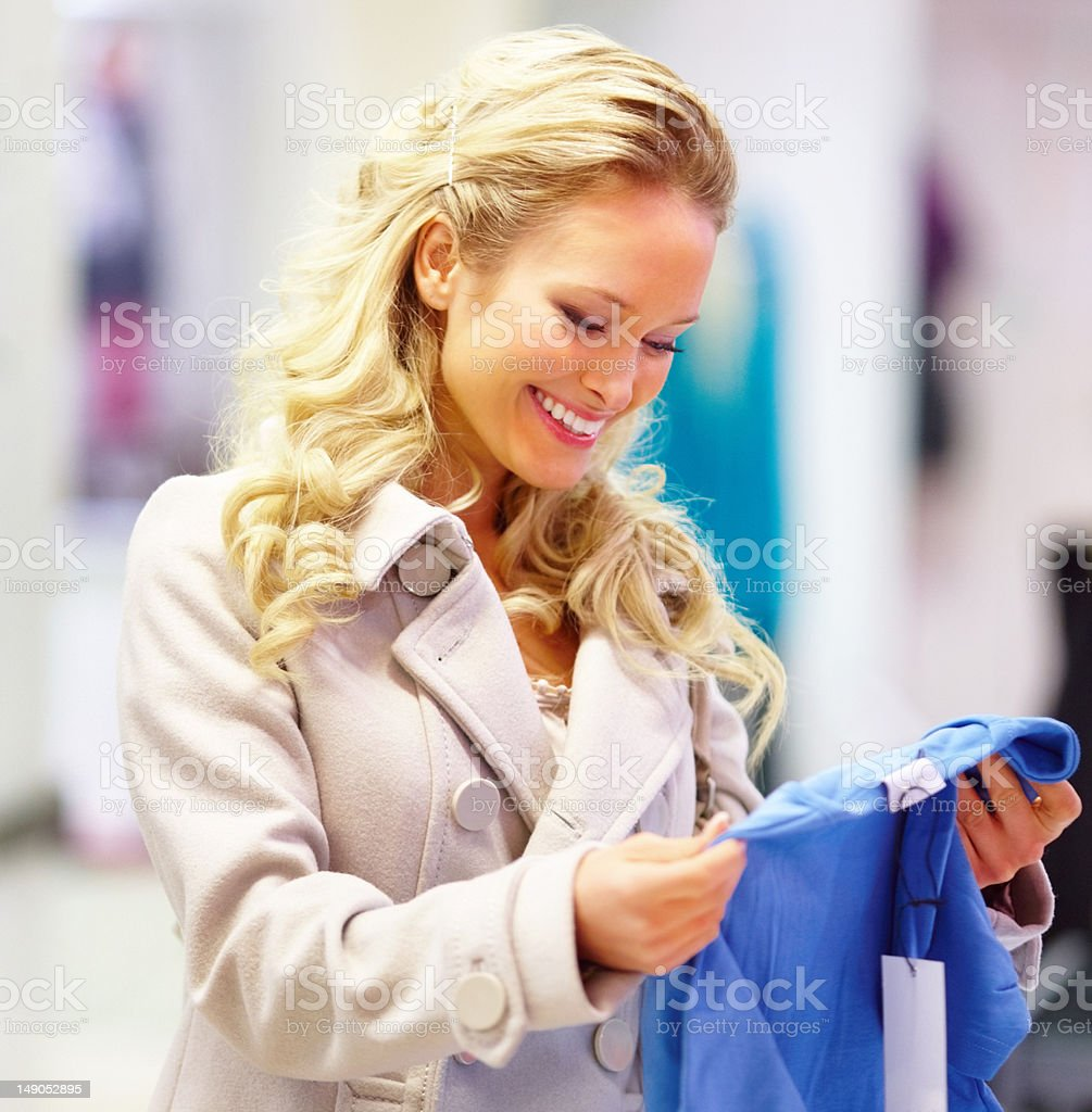 Happy young woman selecting clothes in shop royalty-free stock photo