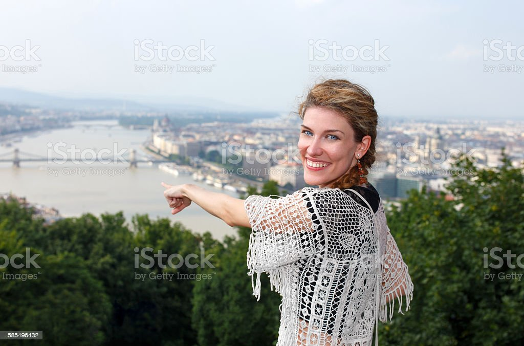 Happy young woman showing away Budapest panorama stock photo