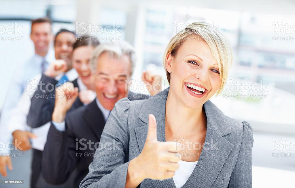 Happy young woman showing thumbs up sign with her team royalty-free stock photo