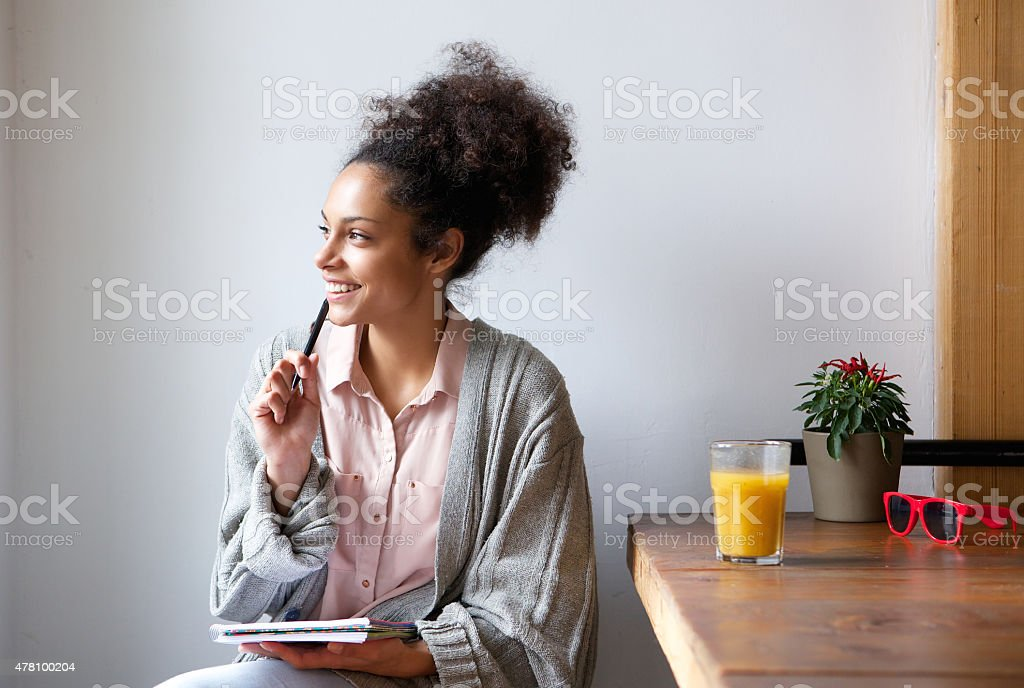 Happy young woman sitting at home with pen and paper stock photo