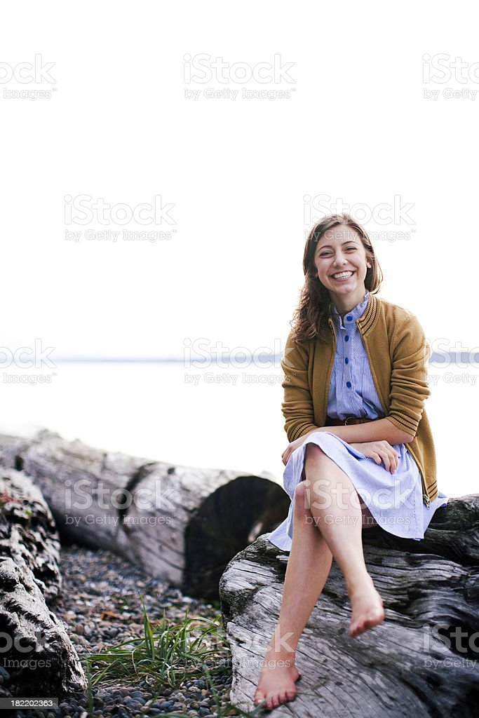 Happy Young Woman Sitting by the Sea royalty-free stock photo
