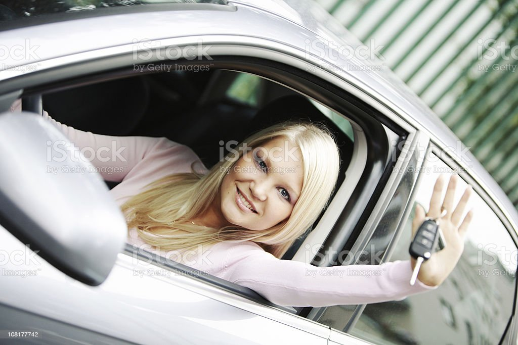 Happy Young Woman Sitting in New Car and Showing Keys royalty-free stock photo