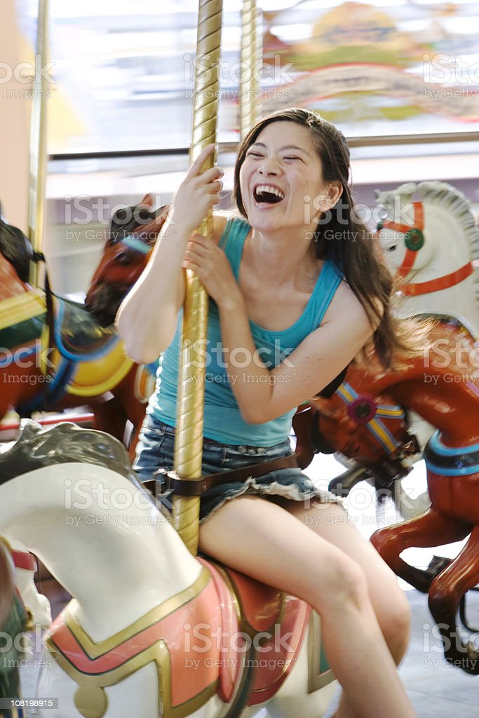 Happy Young Woman Sitting on Carousel Horse stock photo