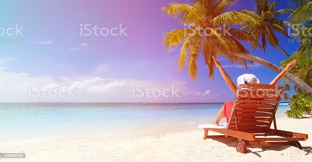 happy young woman sitting on chair at beach stock photo
