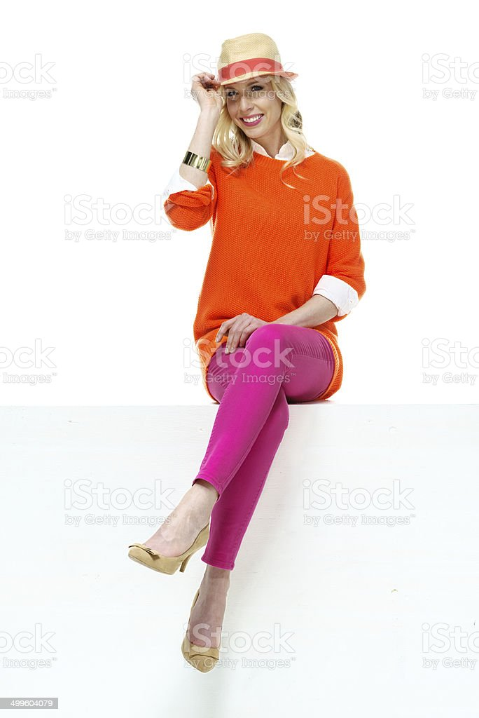 Happy young woman sitting on ledge stock photo