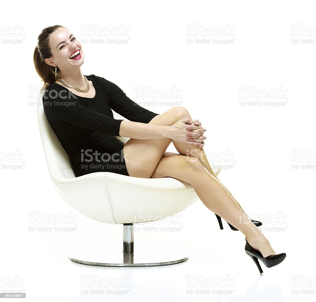 Happy young woman sitting on modern chair stock photo