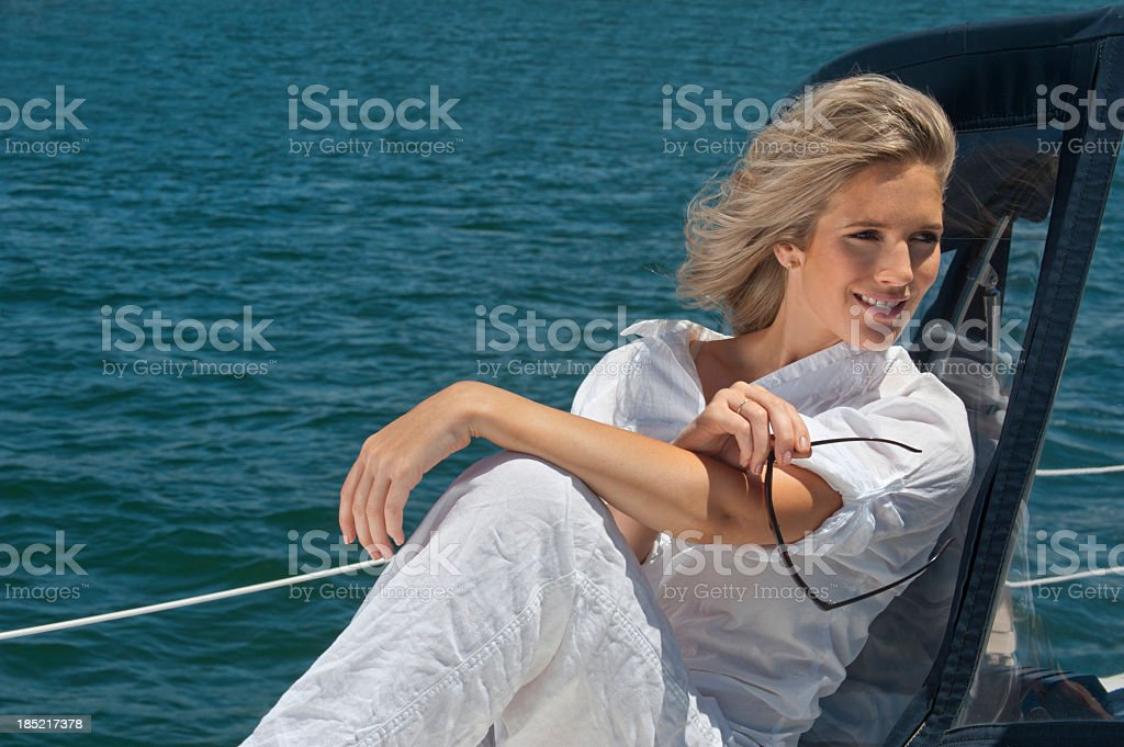 Happy young woman sitting on sail boat royalty-free stock photo