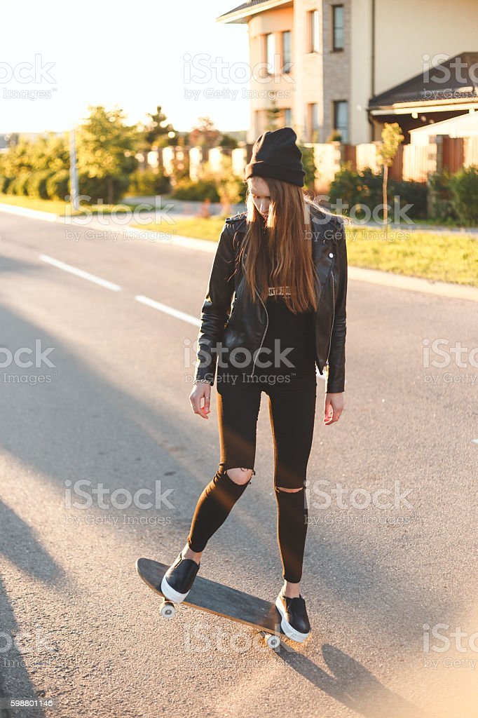 Happy Young Woman Skating On Skateboard, Outdoors stock photo