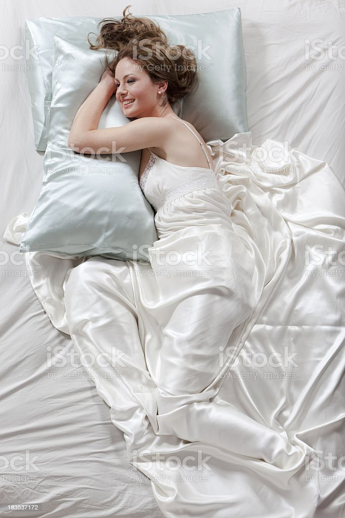 Happy young woman smiling in the bed royalty-free stock photo