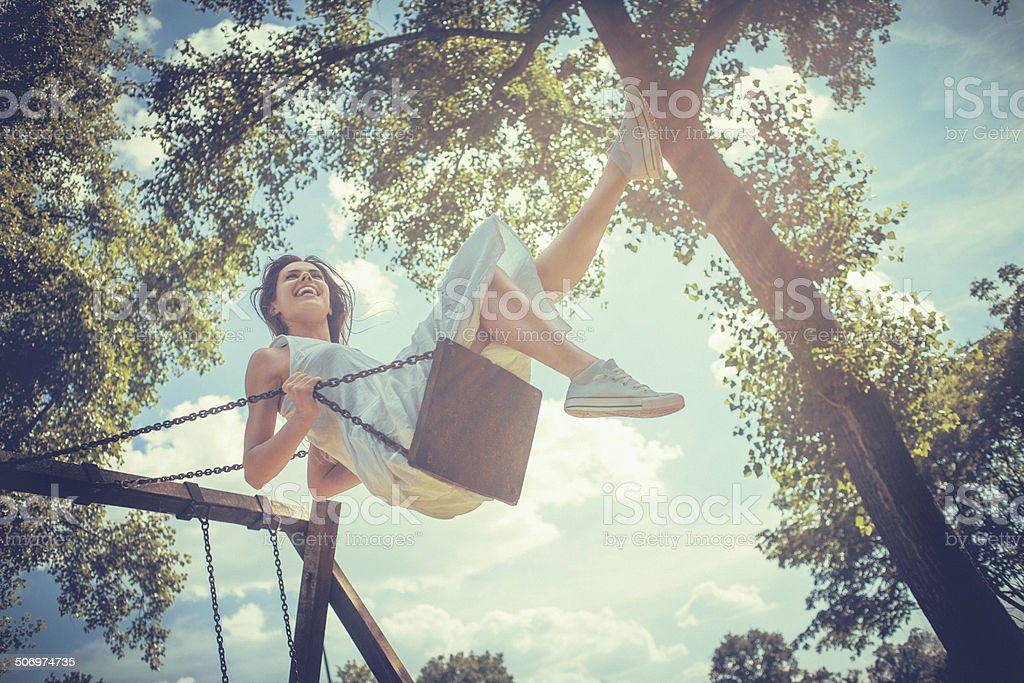 Happy young woman smiling on swing stock photo