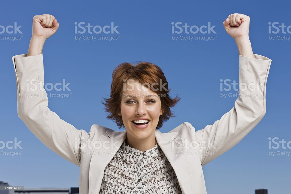 Happy young woman smiling with arms raised royalty-free stock photo