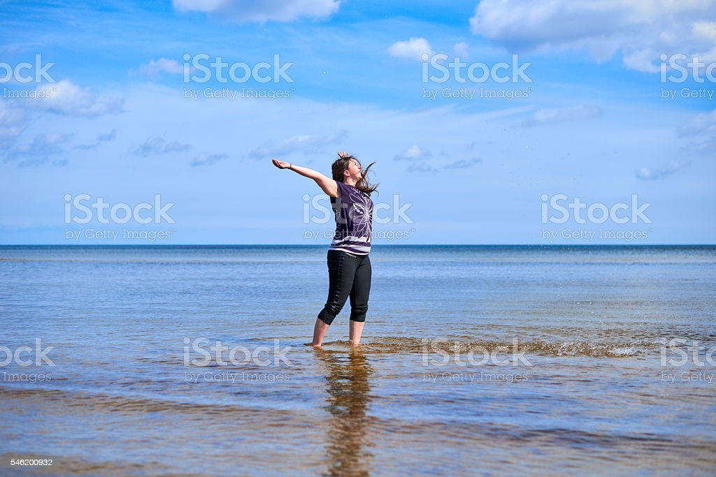Happy young woman sprays water stock photo