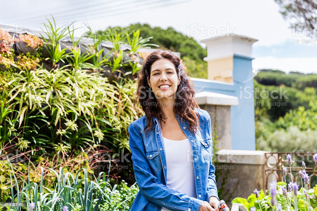 Happy young woman standing in garden stock photo